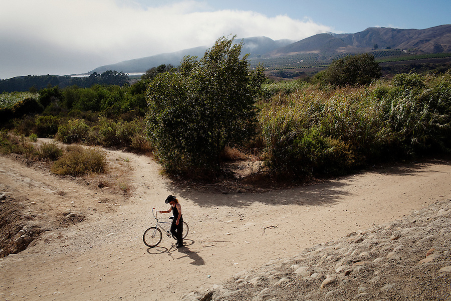 """Ventura, California, July 23, 2010 - Tim 'Timbow' Bowman pushes his bike along the paths of the Ventura River bottom where he has been living in a tent since the early 1990's. In 1987 Bowman's 18-month-old daughter, Miranda Laurel, died from Lyme disease. His wife left him soon afterwards. A year later he fell through a plate glass window while working on a construction site, leaving him disabled and unable to work construction. He says the loss of his wife and daughter and his struggles with work sent him into a spiral. He eventually lost his home. He says he lives in the 300+ community along the river bottom because he """"feels at home."""" Adding, """"I feel loved down here. Up there is nothing but trouble."""" The two-mile stretch of river bottom from the Pacific to Stanley Road is home to about 300 homeless, who have carved tunnels and paths into the tall grass and bamboo. The camps are a controversy because the river is the water source for nearby farms - such as the vineyards in the distance - and is an estuary to thousands of migratory birds. Many feel the camps pollute the river and should me moved to a safer location. .."""