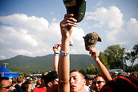 Young men use their hats to get the attention of a friend while a crowd forms to watch the wet t-shirt contest at the Testicle Festival in Clinton, MT.  The Rock Creek Lodge in Clinton, MT, has hosted the annual Testicle Festival since the early 1980s.  The four day festival and party revolves around the consumption of so-called Rocky Mountain Oysters, which are deep-fried bull testicles.