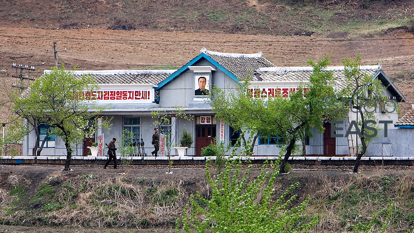 North Korean soldiers carrying rifles walk by a North Korean trainstation showing the portrait of North-Korean leader Kim Jong-Il and the slogan 'Hail to the great leader, comrade Kim Jong-Il!', as seen from a location near Kaishantun, Jilin province, China, on May 10, 2009. When one looks at North Korea from China, North Korean soldiers are always seen around, carrying rifles. Photo by Lucas Schifres/Pictobank