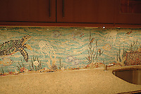 This custom kitchen features a handmade Sea Life mosaic backsplash shown in jewel glass from New Ravenna.<br />