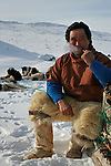 Inuit hunter Kristian Eipe smokes his pipe during a break along the trail as his group moves across an area of tundra connecting two fjords. A changing climate - which shows itself in warming temperatures, earlier summers, later winters, and shrinking and thinning sea ice - threatens the livelihoods and traditions of some of the last subsistence hunters on Earth, the Polar Inuit communities of far Northwest Greenland.