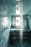 The small Moroccan-style bathroom is covered in a patchwork of aqua blue ceramic tiles and has a traditional Moroccan brass basin