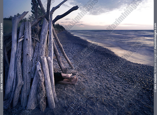 Feet of a couple under a driftwood shack alone on a sea shore at sunset