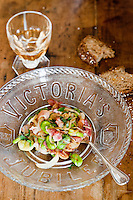 Close up of a broad bean and bacon salad prepared by chef Maddalena Caruso and served on a glass plate commemorating Queen Victoria's Jubilee