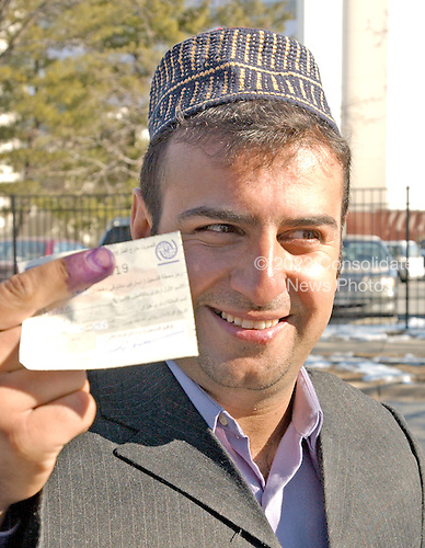 Shwan Hussein, a Kurd from Northern Iraq, proudly displays his voter registration card and purple finger after casting his ballot in the Iraqi election in New Carollton, Maryland on January 28, 2005.  Each voter was required to dip their finger in purple ink to mark that they had voted and were ineligible to vote again.  Mr. Hussein currently resides in Laurel, Maryland.  .Credit: Ron Sachs , CNP..(RESTRICTION: NO New York or New Jersey Newspapers or newspapers within a 75 mile radius of New York City)