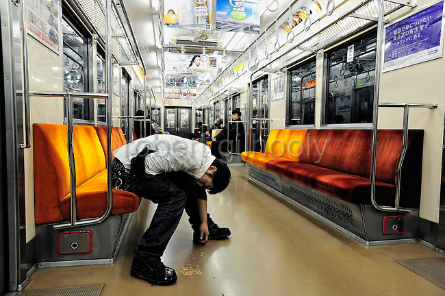 A drunken man sleeps seemingly unaware that he has been vomiting on a train in Tokyo, Japan. The Japanese are well known for their civility and politeness,  but a recent governmental campaign to clamp down on lewd behavior that may inconvenience to others -- including talking on cell phones and applying makeup while commuting on a train -- was fueled by a decline in  everyday etiquette and manners.