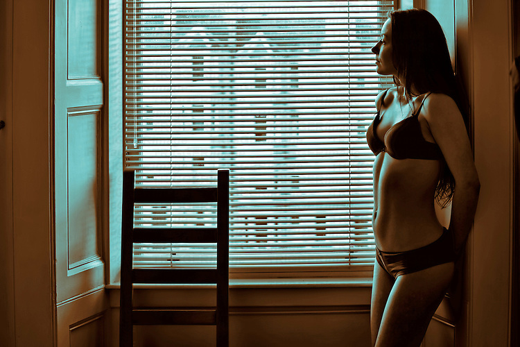 Young woman looking out window from a dimly lit room