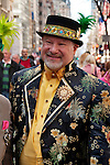 A man in the New York City Easter Parade wearing an embroidered coat and a black hat with an embroidered ribbon and feathers
