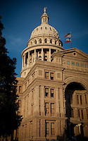 Vibrant Texas State Capitol simmers at sunset in downtown Austin, Texas.