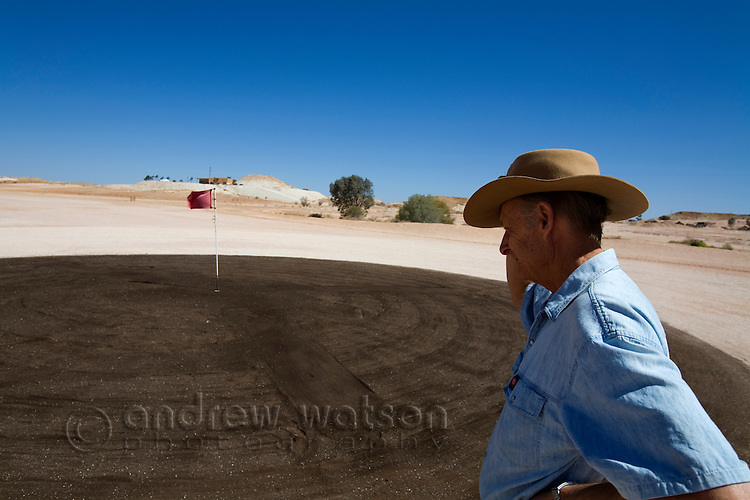 A man inspects a puttting green on the Coober Pedy golf course.  Situated in a desert landscape the golf course is bare earth with oiled sand for the putting greens.  Coober Pedy, South Australia, AUSTRALIA.