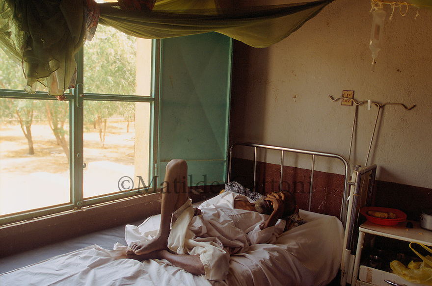 Eritrea - Gash Barka - Old blind man suffering from severe malnutrition lying on his hospital bed. As a result of 30 years of war for independence against Ethiopia (from 1961 to 1991) and another 3 years from 1997 to 2000, there are 50,000 Eritreans currently living in internally displaced (IDP) camps throughout the country. These IDPs have fled three times in the last 10 years, each time because of renewed military conflict. They lived in relatives' homes when lucky enough, but mostly, the fled to the mountains, where they attempted to do what Eritreans do best, survive. Currently there is no Ethiopian occupation in Eritrea, but landmines prevent the IDPs from finally going home. .It is estimated that every Eritrean family lost two or three members to the war which makes the reality of the current emergency situation even more painful for Eritreans worldwide. Currently, the male population has been decreased dramatically, affecting the most fundamental socio-economic systems in the country. Among the refugee population, an overwhelming majority of families are female-headed, severely affecting agricultural production. For, IDPs in particular, 80% of households are female-headed..The unresolved border dispute with Ethiopia remains the most important drawback to Eritrea's socio-economic development, as national resources (human and material) continue to be prioritized for national defense. Eritrea is vulnerable to recurrent droughts and variable weather conditions with potentially negative effects on the 80 percent of the population that depend on agriculture and pastoralism as main sources of livelihood. The situation has been exacerbated by the unresolved border dispute, resulting in economic stagnation, lack of food security and increased susceptibility of the population to various ailments including communicable diseases and malnutrition. .