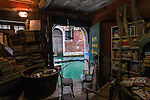 "the backdoor of the libreria - book shop ""Acqua Alta"" (literally, High Water"") in Calle Lunga Santa Maria Formosa, Venice, Italy. One of the most unique bookshops in the world, with gondolas used as bookshelves, a starway with the steps made up of old books, and a back door directly leading on to a canal and ironically called  ""fire exit""."