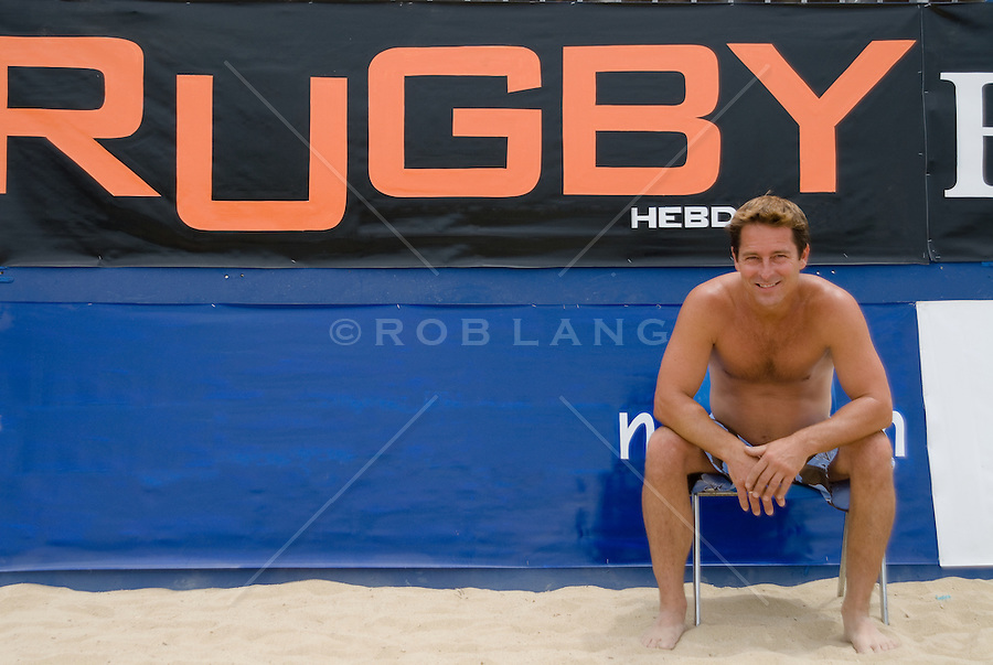 Shirtless man sitting in a chair in front of a Rugby sign