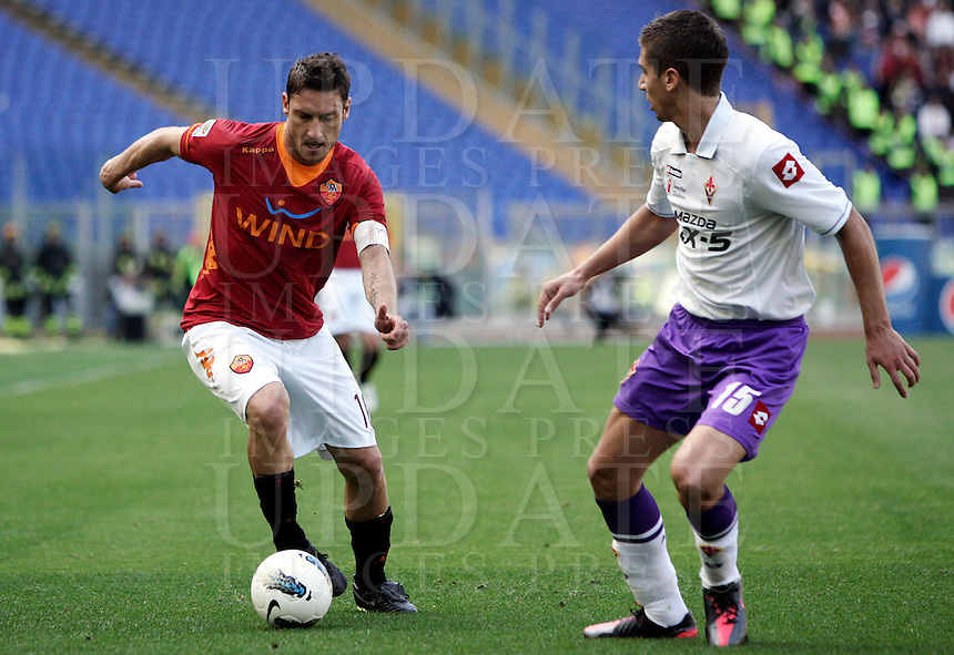 Calcio, Serie A: Roma-Fiorentina. Roma, stadio Olimpico, 25 aprile 2012. Il capitano della Roma Francesco Totti affrontato dal difensore serbo della Fiorentina Matija Nastasic, a destra..AS Roma forward Francesco Totti is challenged by Fiorentina defender Matija Nastasic, of Serbia, right, during the Italian Serie A football match between AS Roma and Fiorentina, at Rome Olympic stadium, 25 april 2012..UPDATE IMAGES PRESS/Riccardo De Luca