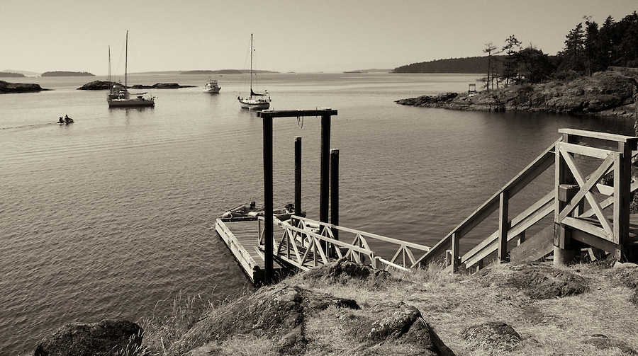 A dock juts into the water facing sailboats at anchor at Portland Island, one of the small islands near Vancouver Island.