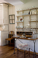 In this corner of the kitchen disparate antique shop finds have been brought together to create a harmonious corner for the storage of glassware and cutlery