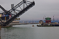 A sailboat makes its way under the raised Lefty O'Doul Bridge and into China Basin next to AT&T Park.