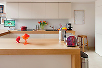 This open plan kitchen is contained by a breakfast bar of thick oak