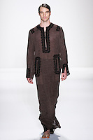 Model walks runway a MEN'S DESERT SILK MOUSSELINE LINEN CAFTAN W/ EBONY FRENCH LACE + RIBBON TRIMS MEN'S, AND DESERT SILK MOUSSELINE LINEN DRAWSTRING TROUSERS by Zang Toi, for the Zang Toi Spring 2012 My Dream Of North Africa Collection, during Mercedes-Benz Fashion Week Spring 2012.