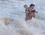 A young boy finds in getting a ride on dad shoulder at Sandy Beach in Hawaii to be very entertaining.