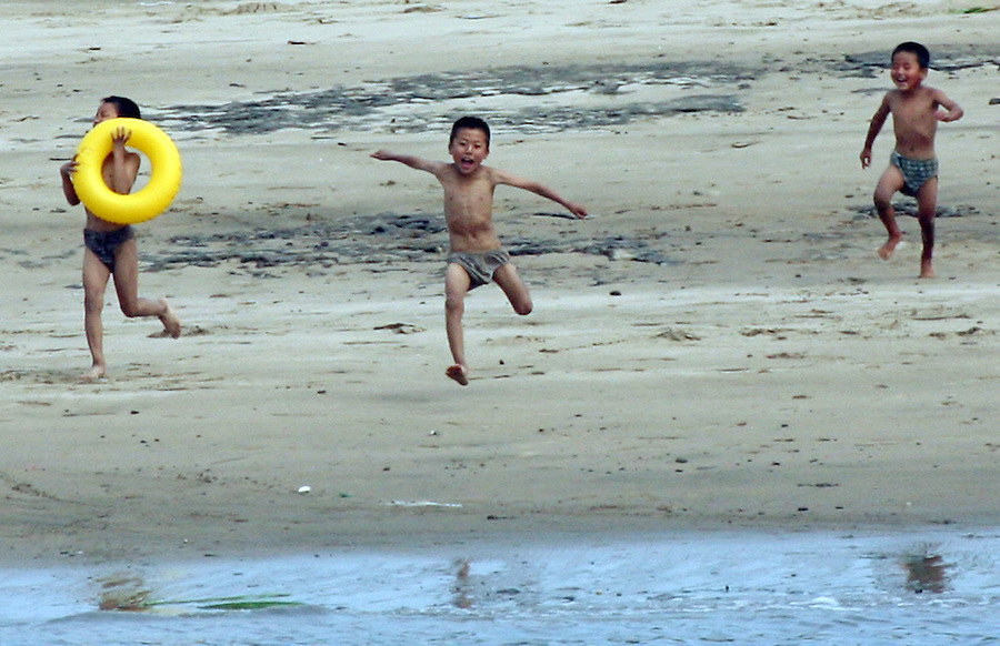 "North Korean gleefully run towards the shore of the Yalu River for a swim in the town of Sinuiju July 8, 2006. China and North Korea are separated by the Yalu River, upon which Chinese tourists take pleaure cruises across the water to  observe their less economically developed neighbors.  North Korea has threatened to take ""stronger physical actions"" after Japan imposed punitive measures in response to its barrage of missile tests and pushed for international sanctions. North Korea has vowed to carry out more launches and has said it will use force if the international community tries to stop it. DPRK, north korea, china, dandong, border, liaoning, democratic, people's, rebiblic, of, korea, nuclear, test, rice, japan, arms, race, weapons, stalinist, communist, kin jong il"
