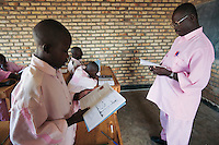 Rwanda. Southern province. District of Muhanga. Central jail of Gitarama.  A black man, working as a teacher and wearing the pink prisoner's clothes and pending trial for the 1994 genocide, and a group of black teenagers boys, during the french class.Bricks wall. Minors block. Minors in detention. Detention pending trial and after trial, sentenced to prison. The non-governmental organization (NGO) Fondation DiDé - Dignité en détention runs the Encademi (Encadrement des mineurs) program. Prison centrale de Gitarama. Quartier des mineurs.  © 2007 Didier Ruef