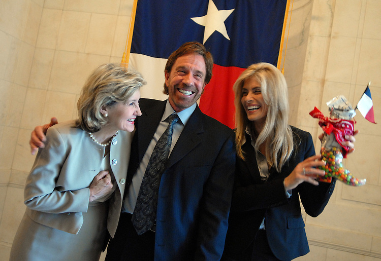 """Actor Chuck Norris, his wife Gena, right, and Sen. Kay Bailey Hutchison, R-Texas, talked to the media in front of the flag of Texas in Russell Building, about the """"Kick Start"""" program.  """"Kick Start"""" is a youth character development program founded by Norris that aims to keep kids off drugs, out of gangs, and builds their self confidence.  The Senator gave the Norris' a care package after the event."""