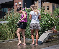"""Visitors to the High Line Park in New York cool off their feet in the """"water feature"""" during the heat wave, on Wednesday, July 17, 2013. The heat wave is expected to last for several more days, finally breaking on Saturday.  Meanwhile, the city has issued a heat advisory and has opened up cooling centers in all five boroughs ( © Richard B. Levine)"""