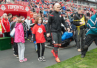 Toronto, Ontario - May 3, 2014: Toronto FC midfielder Michael Bradley #4 walls onto the pitch with a player escort during the opening ceremonies in a game between the New England Revolution and Toronto FC at BMO Field.<br /> The New England Revolution won 2-1.