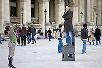 Tourist has his photograph taken balancing on posing plinth outside the Louvre Museum, Paris, France