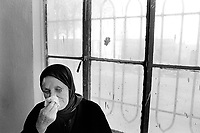 Iraq. Baghdad. Iraqi women league. Fadila Alewi cries when she talks about her husband killed in 1963, because he was a communist, by the Baath party (previous to the Saddam Hussein regime). She wears the hijab, a black veil which covers her hair. The word hijab (or hidjab) refers to both the veil covering the head and traditionally worn by muslim women (Islamic headscarf), but also the  modest muslim styles of dress in general. 20.02.04 © 2004 Didier Ruef .