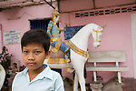 Bunroeun visits the local Buddhist pagoda..A Khmer boy learns to play classical violin at the college of Beaux Arts, at the edge of Cambodia's capital, Phnom Penh. He is an orphan and comes from a poor family. His parents died long ago, from AIDS related diseases. He lives with his grandmother and his uncle, and their family. He lives on the top floor of an apartment block, where his family run a textile business, sewing together clothes and ornamental flags from around the world. A dozen young women work in this textile business, and the boy's home space is actually amidst this small factory environment which he shares with them. They eat, work and play together like an extended family or community. Phnom Penh, Cambodia