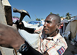 A homeless earthquake survivor builds a temporary shelter in an already crowded soccer stadium in the Santa Teresa area of Petionville, Haiti. Hundreds of thousands of Haitians were left homeless by the January 12 quake.