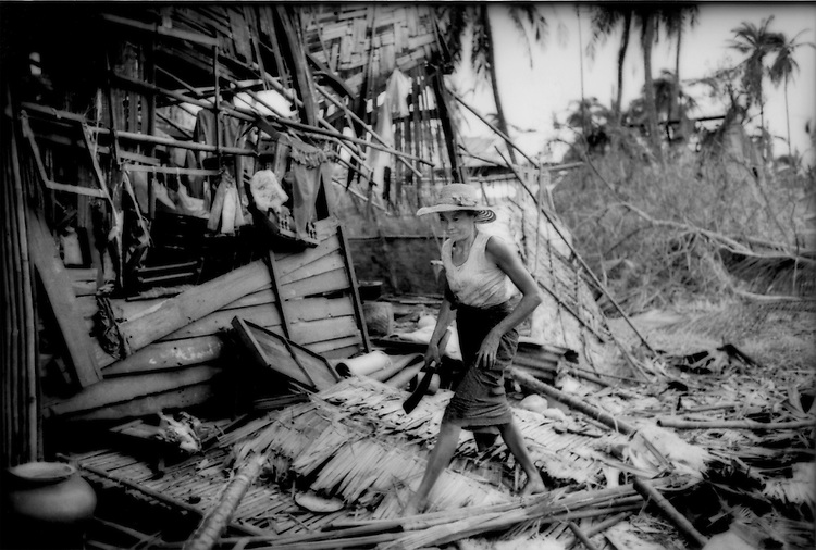 Woman walks carefully over what used to been the palm thatched roof of her home which was badly damaged (rear) by Cylcone Nargis in the Irrawaddy River Delta, Kyaiklat, Burma (Myanmar).