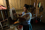 Mayan woman pours corn into a grinder to make a fine flour for preparing tortillas.  She lives in traditional village of Midway in southern Belize.