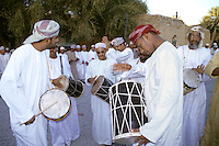 Al-Hamra, Oman, Arabian Peninsula, Middle East - Omanis perform the ar-Razha dance.  This dance is performed at weddings or, in this case, to celebrate the Eid al-Adha (Feast of the Sacrifice), the annual feast through which Muslims commemorate God's mercy in allowing Abraham to sacrifice a ram instead of his son, to prove his faith.  Musicians are wearing traditional Omani dishdashas and wearing kummas, traditional embroidered Omani hats, or massars, the Omani turban.