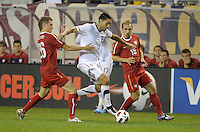 US midfielder Clint Dempsey (8) plays the ball in between Poland defender Lukasz Piszczek (26) and midfielder Adrian Mierzejewski (18).  The U.S. Men's National Team tied Poland 2-2 at Soldier Field in Chicago, IL on October 9, 2010.