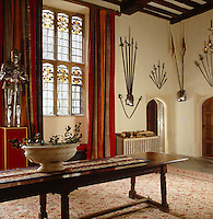 Weapons and suits of armour decorate the etrance hall which features mullioned windows with coloured glass crests