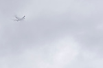 Jet airliner flying through low clouds