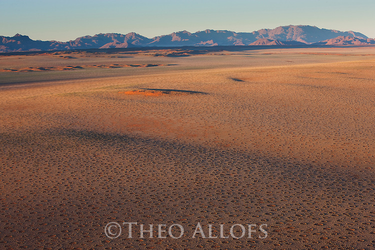 Namibia, Namib Desert, Namibrand Nature Reserve, aerial view of fairy circle plain and mountains in background