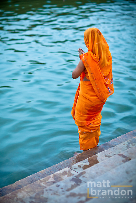 A woman offers prayers on the edge of the Ganges River in the ancient city of Varanasi or Benares