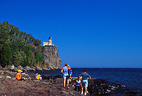 TOURISTS VIEW THE THE SPLIT ROCK LIGHTHOUSE FROM BELOW AT SPLIT ROCK LIGHTHOSE STATE PARK NEAR TWO HARBORS, MINNESOTA.