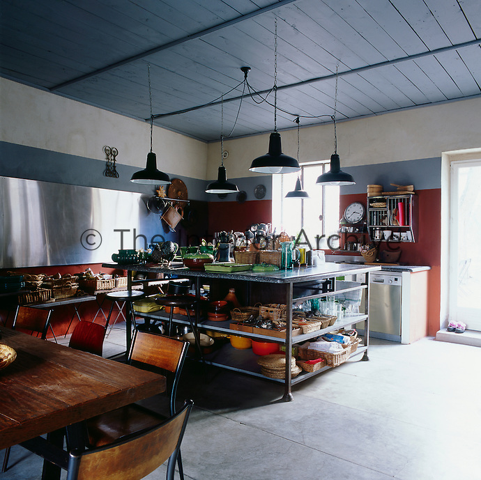 A spacious kitchen dining space with a grey painted wood panelled ceiling and red walls. Metal lamps hang above a metal unit with shelves below that a central storage point for all manner of kitchenware. A stainless steel panel is fixed against one wall. A wood table and chairs provides a spot for dining.