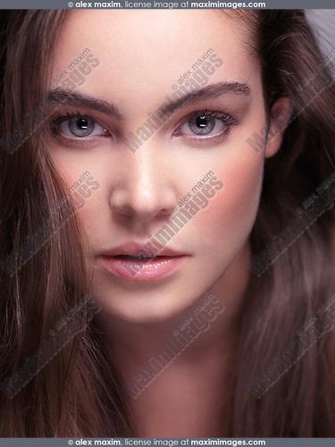 Beautiful young woman face with natural makeup, gray eyes and brown hair looking at camera