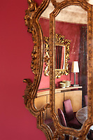 Antique gilt-framed Italian mirrors capture the reflections in this circular dining room