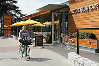 Female cyclist passing the new Cactus Club Cafe on Beach Avenue, Vancouver, British Columbia, Canada