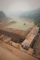 Daytime vertical view from the Sānménxiá Dam of a bridge on the Huang He and a power plant facility in the Sānménxiá Shì Húbīn District in Hénán Province.  © LAN