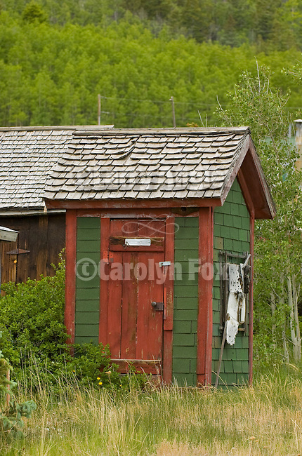 Green wooden outhouse with red door in the Colorado Rockys
