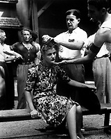 This girl pays the penalty for having had personal relations with the Germans.  Here, in the Montelimar area, France, French civilians shave her head as punishment.  August 20, 1944. Smith.  (Army)<br /> Exact Date Shot Unknown<br /> NARA FILE #:  111-SC-193785<br /> WAR &amp; CONFLICT BOOK #:  1259