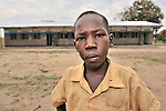 Enosa Likambo, 10, stands in front of his school in Nyei, a village in SOuthern Sudan where people have returned after years in exile to rebuild their land after a devastating civil war. The school was constructed by the United Methodist Committee on Relief (UMCOR).